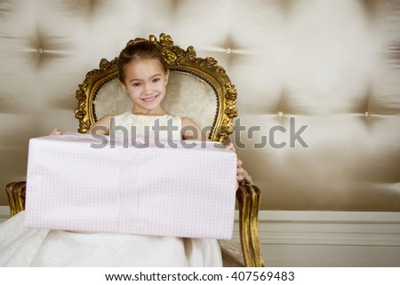 Little girl sitting in an ornate chair wearing a party dress holding a large present - stock photo