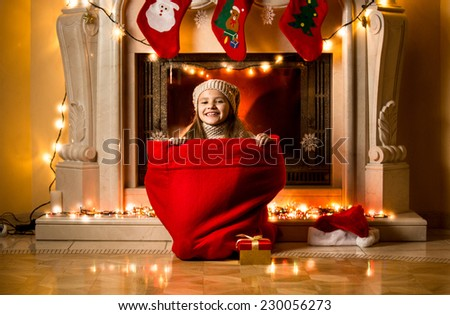 Little girl sitting in big red sack at room decorated for Christmas - stock photo