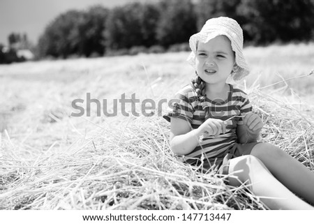 Little girl sitting in mown wheat. Black and white. - stock photo