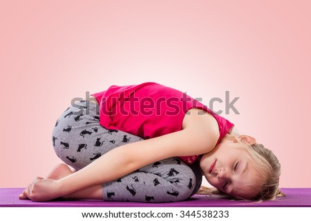 Little girl sitting in yoga pose over color background. - stock photo
