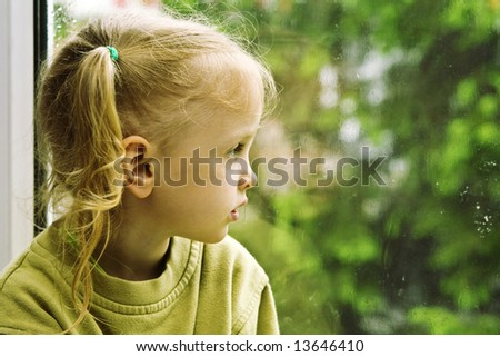 Little girl sitting near the window in the rainy day - stock photo