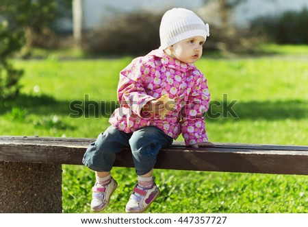 Little girl sitting on a bench and eating bread in nature. Selective focus - stock photo