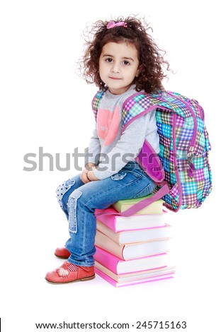 Little girl sitting on a pile of books.Isolated on white background. - stock photo