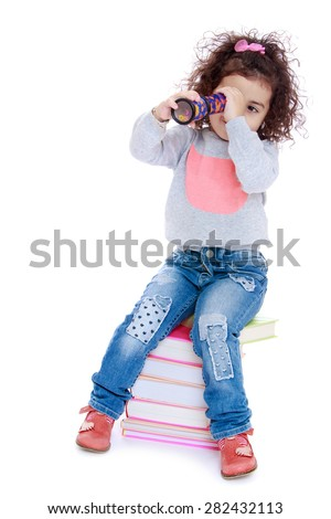 Little girl sitting on a stack of books and looks through a kaleidoscope- isolated on white background - stock photo