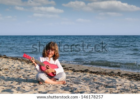little girl sitting on beach and play guitar - stock photo