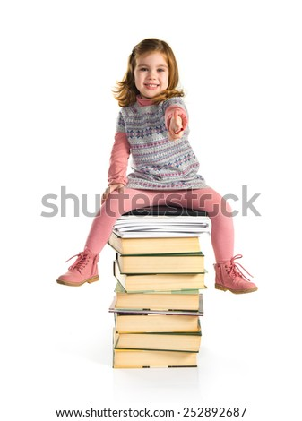 Little girl sitting on books with thumb up - stock photo
