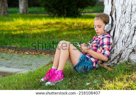 Little girl sitting on grass near a tree and listening to the music using big headphones  in early autumn . - stock photo
