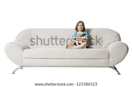 Little girl sitting on sofa with a teddy bear - stock photo