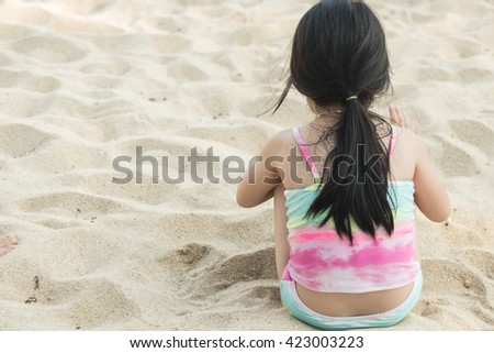 Little girl sitting on the beach with his back to the camera in summer sunny day - stock photo