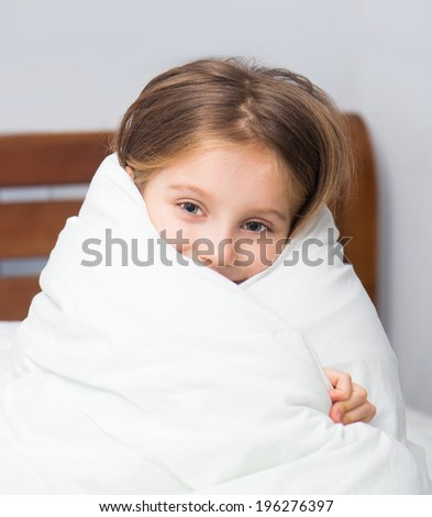 Little girl sitting on the bed wrapped in a blanket - stock photo