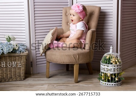 Little girl sitting on the chair at home - stock photo