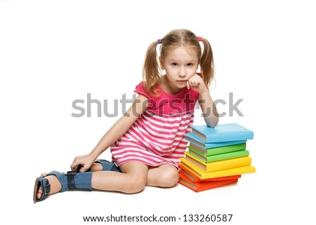 Little girl sitting on the floor leaning on the stack of books, over white background - stock photo