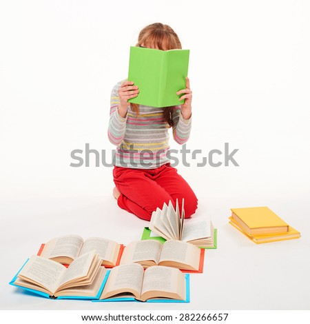 Little girl sitting on the floor with a lot of books, covering the face with a book reading, over white background - stock photo