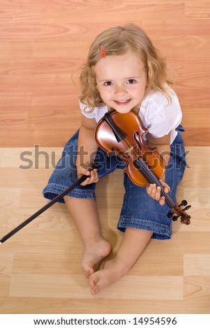 Little girl sitting on the floor with a violin - stock photo