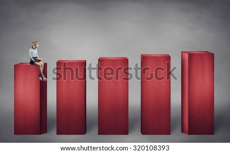 little girl sitting on the lower stage and reading a book - stock photo