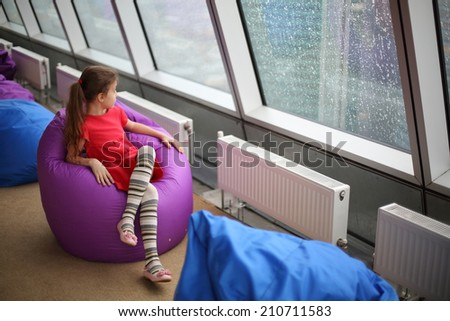 Little girl sitting on the ottoman and looking in large window on a rainy day - stock photo