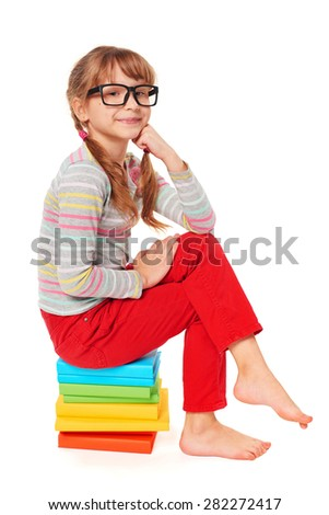 Little girl sitting on the pile of multicolor books, making proud satisfied face, over white background - stock photo