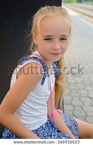 Little girl sitting on the railway platform on the bench - stock photo