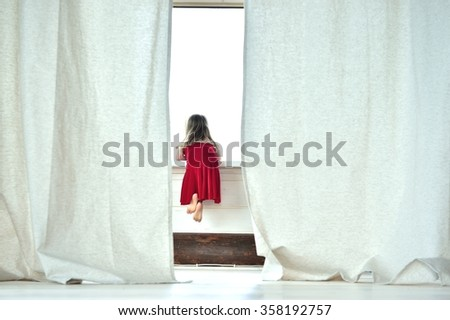 Little girl sitting on the windowsill of a large window  and look outside on outdoors in a day - stock photo