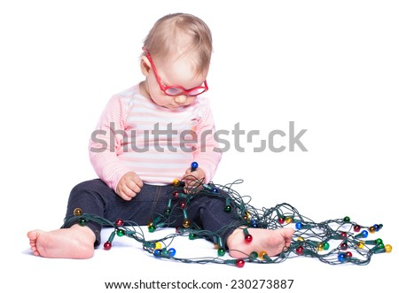 Little girl sitting on white background and playing with Christmas lights. Isolated on white  - stock photo