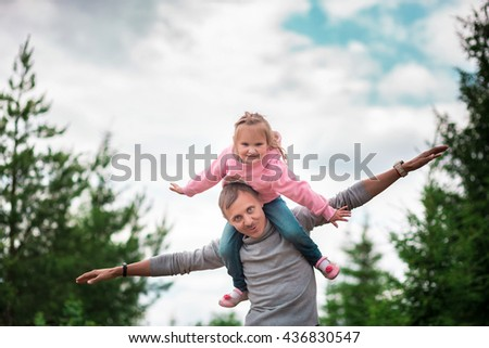 Little girl sitting on your dad shoulders outdoor in the woods during the summer - stock photo