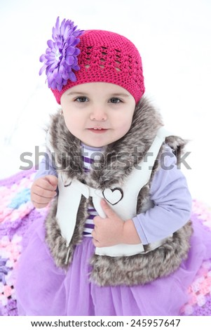 Little girl sitting outside in the snow - stock photo