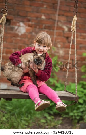Little girl sitting with a cat on the swing - stock photo