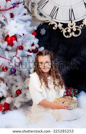 Little girl sitting with nice present under the Christmas tree; adorable child smiling nearby Christmas tree; white fir-tree decorated with red balls and socks - stock photo