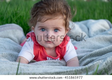 Little girl (six months old) with beautiful blue eyes is lying on the grass. - stock photo