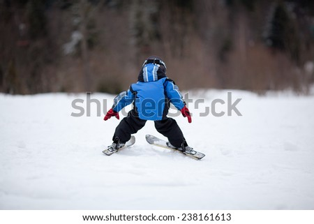 Little girl skiing down the ski slope. Back view - stock photo