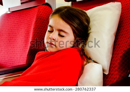 Little girl sleeping in a plane during air travel flight. - stock photo