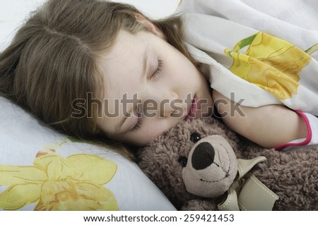 Little girl sleeping in her bed with teddy bear - stock photo