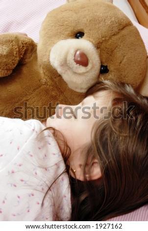 little girl sleeping with a plush bear - stock photo