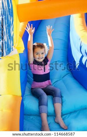 Little Girl sliding down an inflatable Slide - stock photo