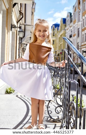 Little girl small baby pretty face wear fashion dress walk on sun city street building summer weather kid child young and beauty happy daughter play fun clothes collection - stock photo