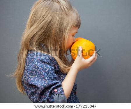 Little girl smelling a ripe orange, grey background - stock photo