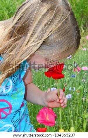 Little girl smelling flowers - stock photo