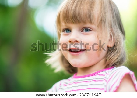 Little girl smiling - adorable young girl looking at camera. - stock photo