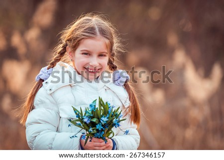 little girl smiling and holding a bouquet of blue  flowers - stock photo