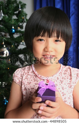 Little girl smiling and holding purple gift box - stock photo
