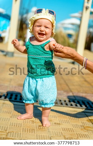Little girl smiling on unfocused background. The little girl is in full growth and smiling. 8 months of age. beautiful baby - stock photo