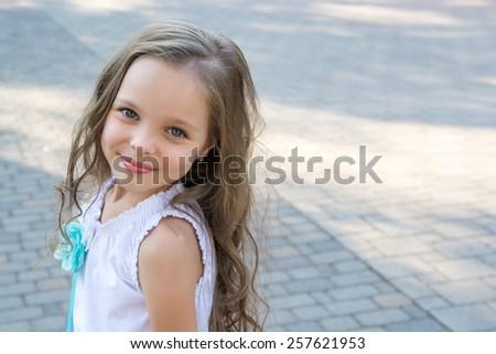 little girl smiling outdoor, front of tile carpet - stock photo