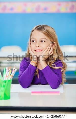 Little girl smiling while sitting with head in hands at classroom desk - stock photo