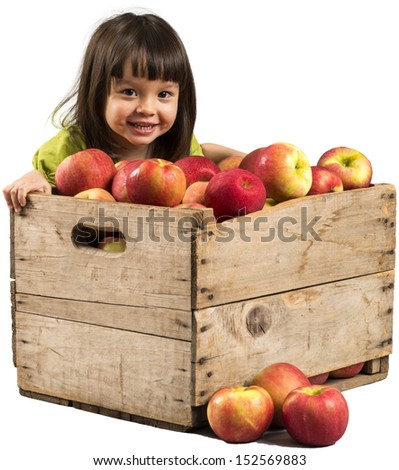 Little girl smiling with crate full of apples. - stock photo