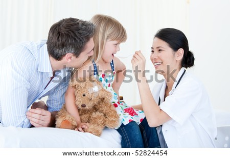 Little girl smiling with her teddy bear against white background - stock photo