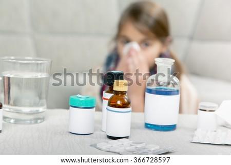 Little girl  sneezing In to tissue - stock photo