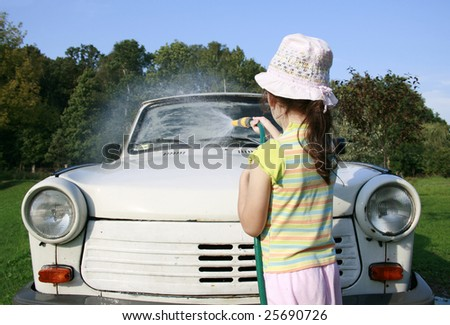 little girl spraying a car with a water hose in a sunny afternoon, rubber hose, pour water on over - stock photo