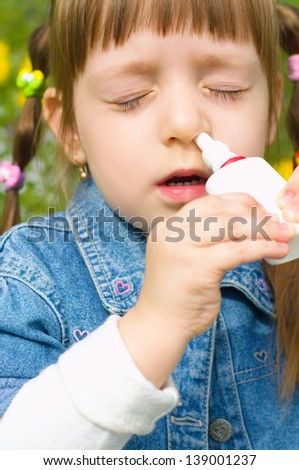 little girl spraying her nose outdoors - stock photo