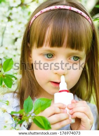 Little girl spraying medicine in nose, nose drops, nose spray. - stock photo