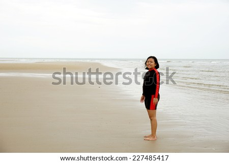 Little girl standing by the sea - stock photo
